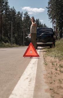 Dreieck-vorsichtsschild auf der straße nach autoausfall und ma sprechen auf dem smartphone, das auf reparaturservice wartet...