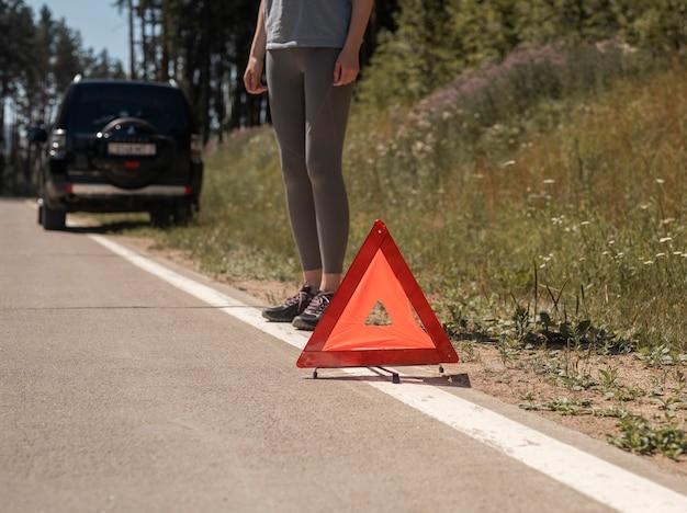 Dreieck-vorsichtsschild hautnah auf der straße nach autopanne und fahrerin, die in der nähe steht