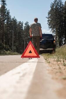 Dreieck-warnschild am straßenrand auf weißer linie in der nähe von kaputtem auto mit fahrer, der weggeht