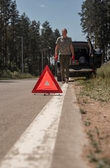 Dreieck-warnschild auf der straße in der nähe eines kaputten autos mit einem mann, der darauf zugeht