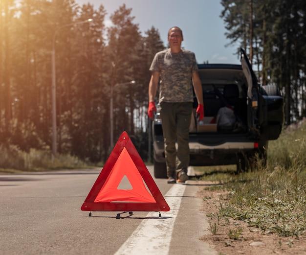 Dreieck-warnschild auf der straße in der nähe von kaputtem auto mit fahrer, der darauf zugeht