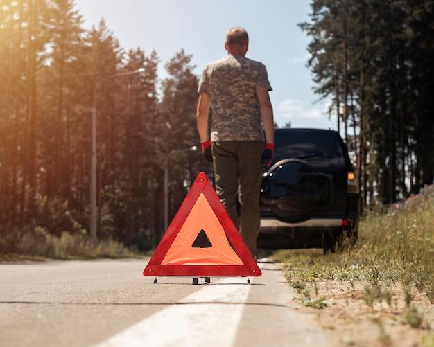 Dreieck-warnschild auf der straße in der nähe von kaputtem auto mit fahrer, der weggeht