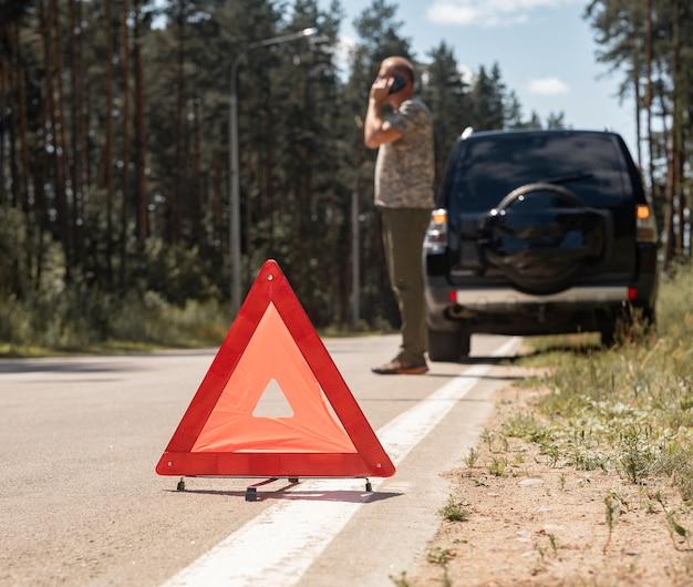 Dreieck-warnschild auf der straße nach einer autopanne und fahrer, die telefonieren und auf den notfall warten...