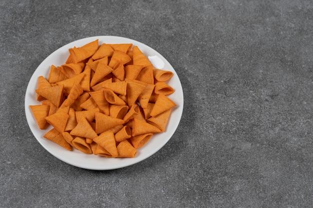 Dreieckige chips auf weißer platte.