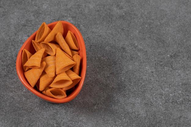 Dreieckige cracker in orangefarbener schüssel.