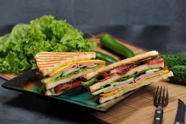 Dreieckige sandwiches mit schinken und omelett auf einem teller