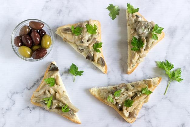 Dreieckige sandwiches mit sommerpilzen, gekocht mit sahne und kräutern, serviert mit oliven.