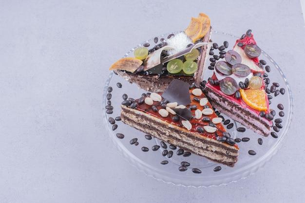 Dreieckige schokoladenkuchenscheiben mit nüssen und früchten in einer glasplatte mit bohnen