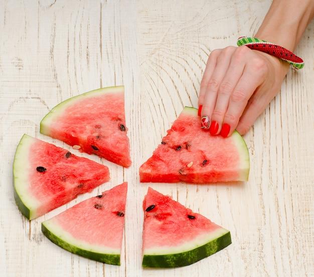 Dreieckige stücke der hände der wassermelone und der frau mit einer maniküre auf einem hellen hölzernen