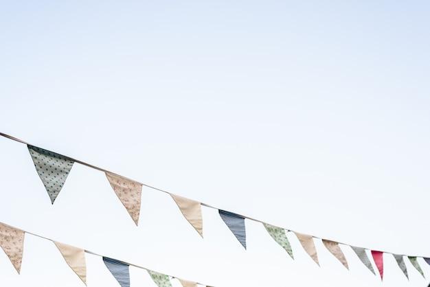 Dreieckige wimpel der weinlese, die mit dem blauen himmel im hintergrund hängen.