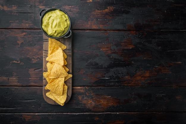 Dreieckiger gelber maistortillachip mit saucen, auf altem holztisch, draufsicht oder flacher lage