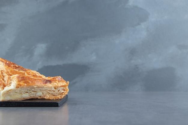 Dreieckiges gebäck gefüllt mit käse auf holzbrett.