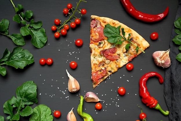 Dreieckiges stück gebackene pizza mit champignons, geräucherten würstchen, tomaten und käse,