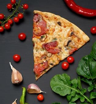 Dreieckiges stück gebackene pizza mit champignons, geräucherten würstchen, tomaten und käse