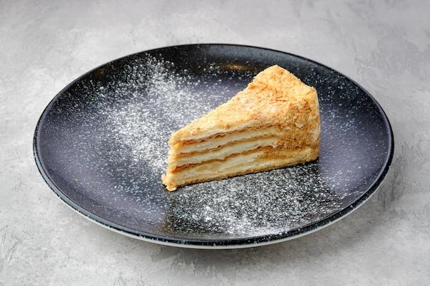 Dreieckiges stück klassischer napoleon-torte auf einem teller