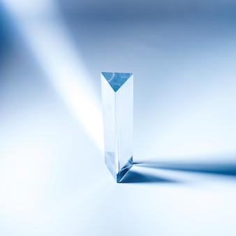 Dreieckiges transparentes prisma mit schatten auf blauem hintergrund