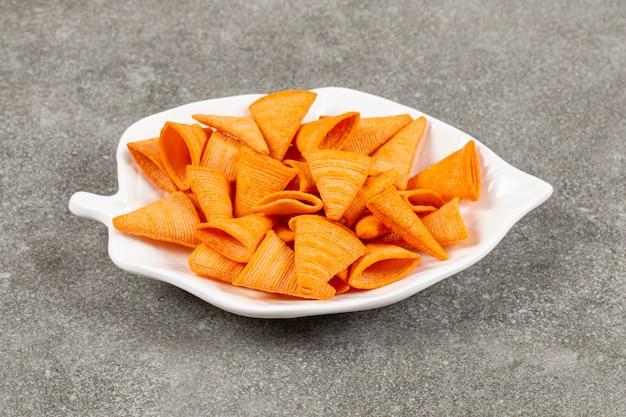 Dreiecksform-chips auf weißer platte.