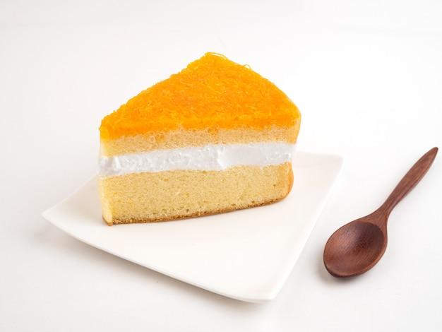 Dreiecksform schneidet stück orangenkuchen und holzlöffel auf weiß