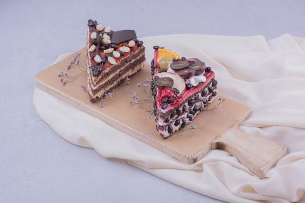 Dreieckskuchenscheiben mit schokolade und früchten auf einem holzbrett