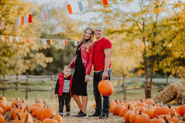 Dreierfamilie mit schwangerer mutter und mutigem vater, der auf dem kürbisfeld aufwirft