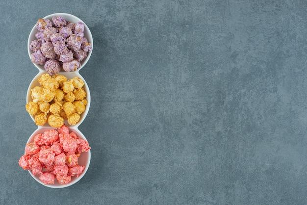 Dreifach-servierplatte mit verschiedenen popcorn-süßigkeiten auf marmorhintergrund. foto in hoher qualität