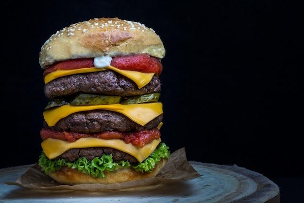 Dreifacher cheeseburger mit tomaten, salat, gurken und mayonnaise