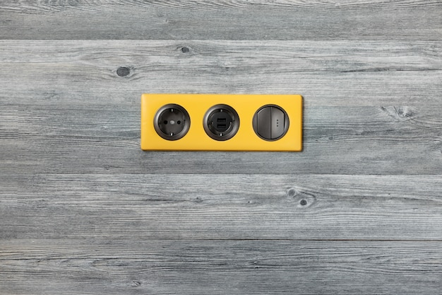 Dreifacher heller gelber rahmen mit steckdose, usb-anschlüssen und hellem schlüsselschalter auf grauer hölzerner wand.