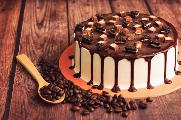 Dreifacher schokoladeneis-kuchen mit kaffeebohnen auf holztisch