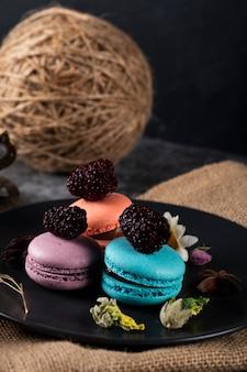 Dreifarbige französische macarons in einer schwarzen untertasse