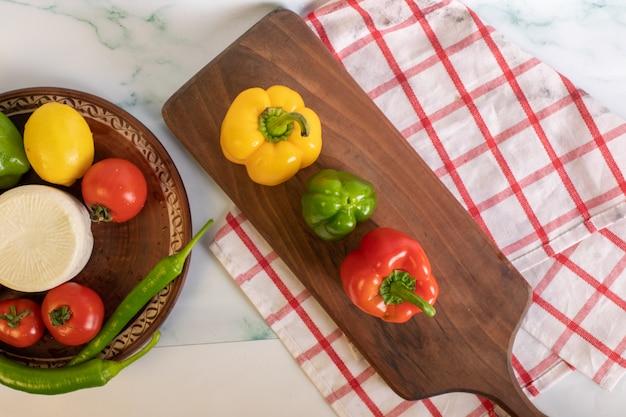 Dreifarbige paprika auf holzbrett. draufsicht