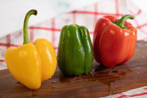 Dreifarbige paprika auf holzbrett