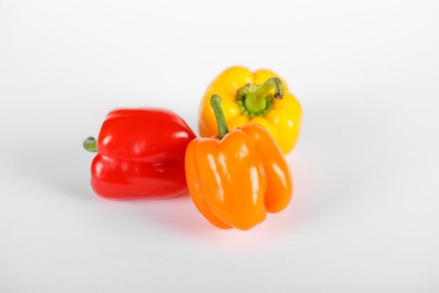 Dreifarbige paprika auf weiß. draufsicht