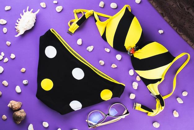 Dreifarbiger badeanzug schwarz-weißer und gelber badeanzug mit kreisen auf einem lila hintergrund