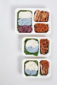 Dreifarbiger klebreis mit gebratenem schweinefleisch und zerkleinertem schweinefleisch in einer weißen plastikbox, auf einer weißen tischdecke, einer lebensmittelbox und thailändischem essen.