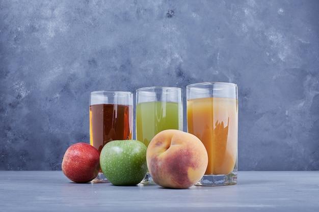Dreifarbiger saft aus drei verschiedenen früchten.
