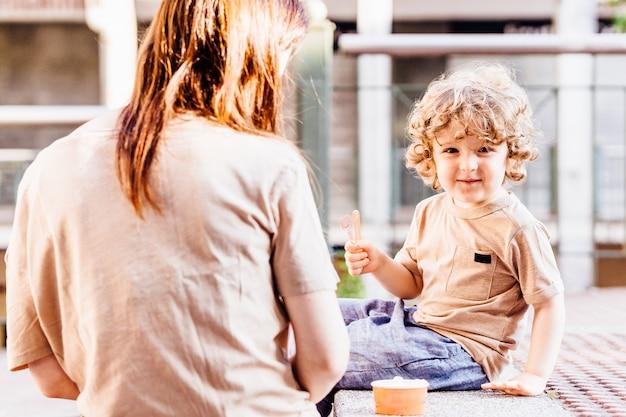 Dreijähriger blonder junge mit schönen locken glücklich mit seiner mutter, nachdem er im sommer auf der straße eis gegessen hat. konzeptpläne mit kindern im sommer im urlaub