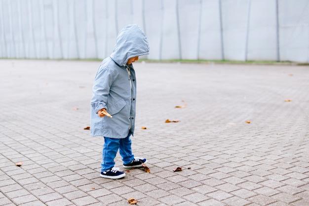 Dreijähriger junge auf der straße im herbst, der in der stadt auf trockene blätter auf dem boden tritt