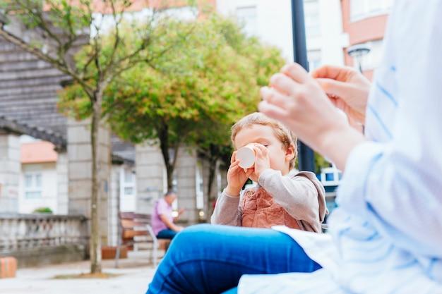Dreijähriger junge, der mit seiner mutter auf der straße einen becher eis mit dem mund schneidet