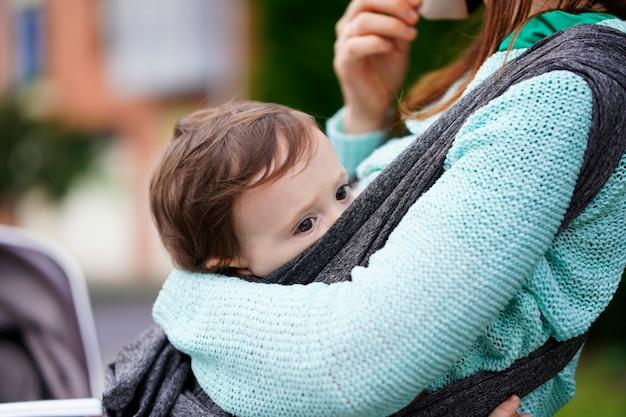 Dreijähriges baby, das von seinem tausendjährigen mutterporträt getragen wird