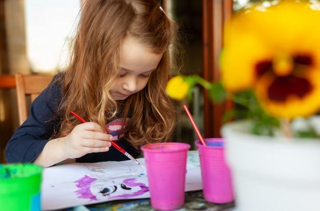 Dreijähriges mädchen malt mit aquarellen auf der terrasse.