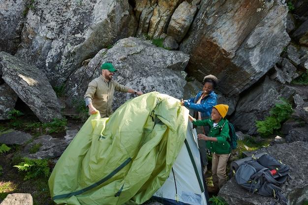 Dreiköpfige familie baut das zelt auf den felsen während ihres campings im freien auf