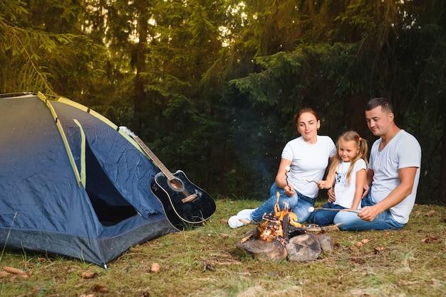 Dreiköpfige familie, die kampiert und spaß beim kochen über feuer hat