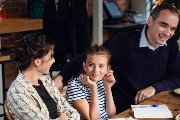 Dreiköpfige familie, die sich an einem esstisch erfreut