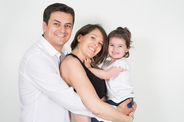 Dreiköpfige familie mit tochter, alleinerziehendes kind, mutter und vater umarmen sich