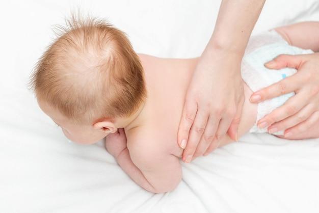 Dreimonatiger junge, der eine rückenmassage von einer massagetherapeutin erhält