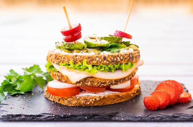 Dreischichtiges sandwich mit verschiedenen gemüsesorten, putenfleisch und avocado im vollkornbrot