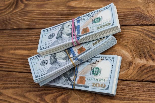 Dreißigtausend dollar in sätzen auf einem tisch mit strukturierten brettern. von oben betrachten.