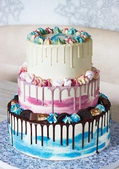 Dreistufiger bunter kuchen mit farbigen flecken der schokolade auf einem licht. bild für ein menü oder einen süßwarenkatalog mit kopienraum
