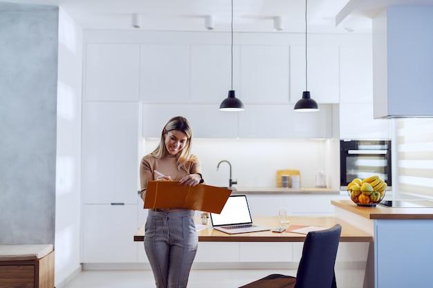 Dreiviertel länge der kaukasischen blonden hübschen geschäftsfrau im pullover, der sich auf küchentisch stützt und statistiken aufschreibt. auf dem küchentisch liegt laptop und papierkram.
