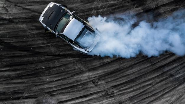 Driftendes auto der draufsicht, treibendes auto des luftfahrtreibenden fahrers auf rennstrecke.